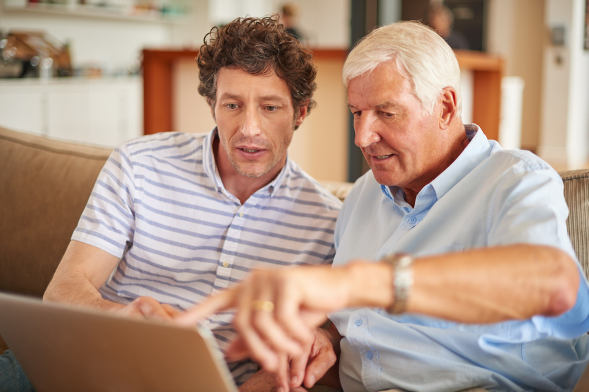 Father and son looking up hearing aid apps online