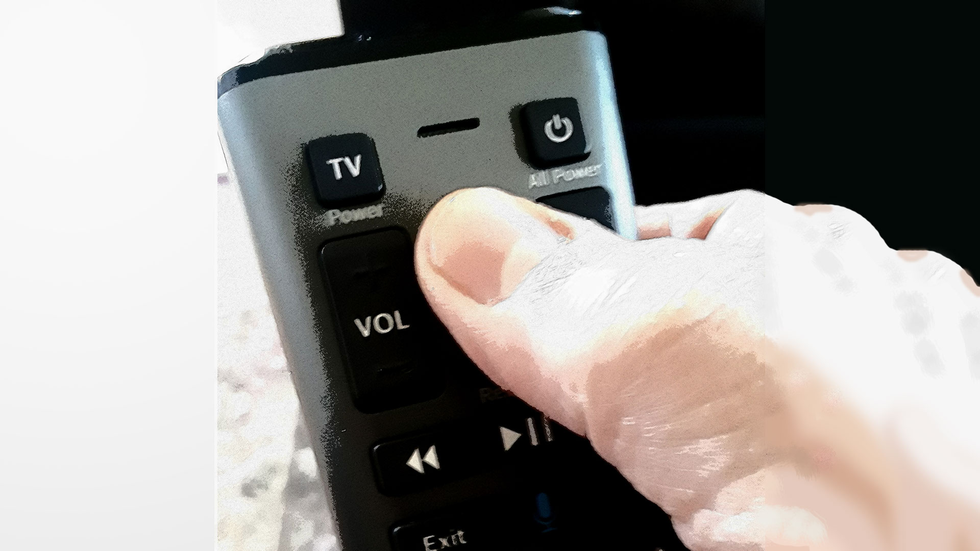 an elderly hand holding and using a specialized TV remote