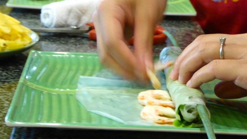 eine Köchin in Hanoi rollt vietnamesische Frühlingsrollen