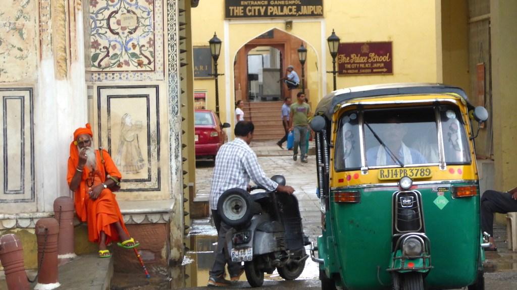 Straßenszene in Jaipur in Indien mit Sadhu und TukTuk