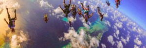 Skydiving angle jump with many skydivers above the Maldives.