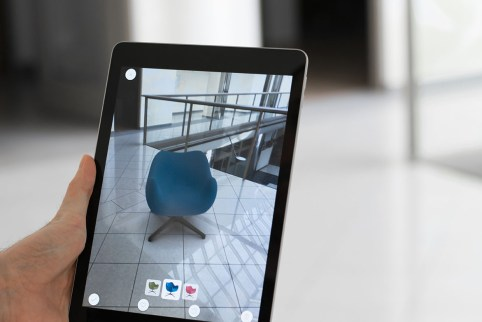 Augmented reality application - man placing furniture in AR space holding a tablet