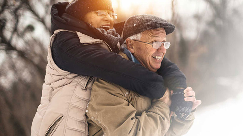an elderly couple enjoys the winter weather together because they prepared their hearing aids for optimal functioning