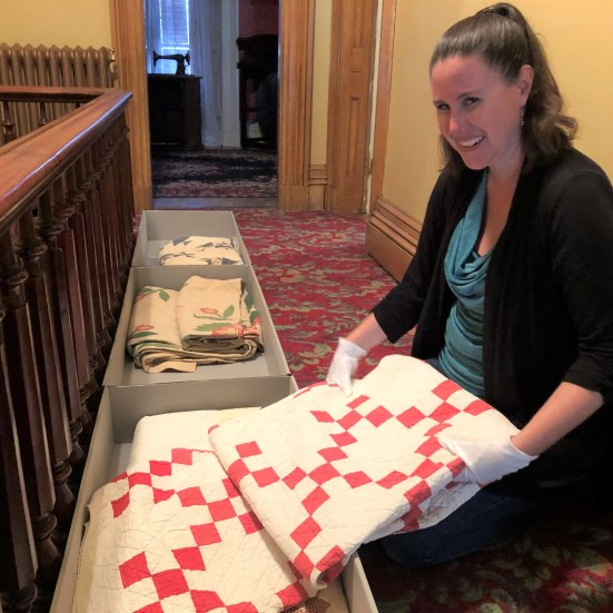 Visiting curator Erin Howard, in the bedroom hallway of the Tanner House Museum, prepares to transport 19th century quilts.