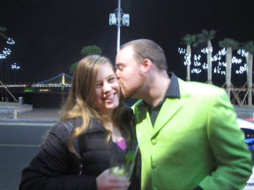 Green suit kissing girl