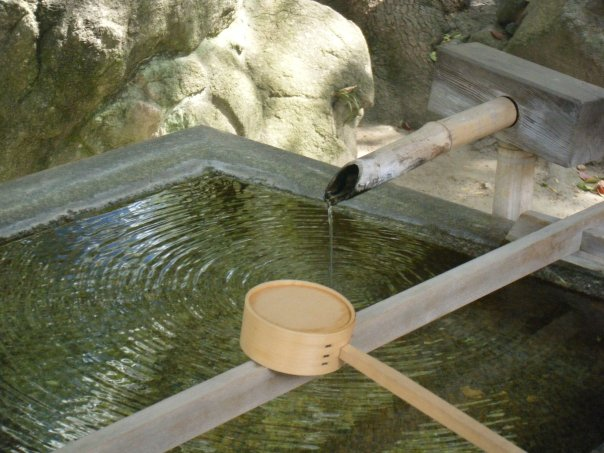 Fresh water trickles into a trough within the temple walls