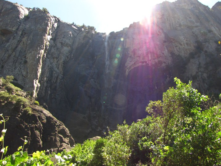 The sun peaks over the cliffs above Bridalveil Falls