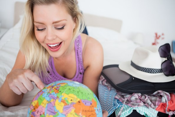 Woman with a suitcase pointing on a globe