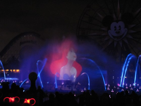 """Ariel singing the beautiful """"Part of Your World"""" projected against the fountains."""