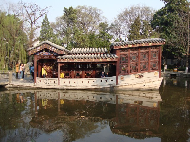 A serene pond and boat shaped building in the Presidential Palace gardens.