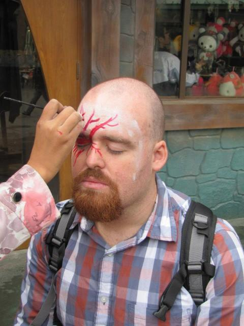 I call on my years of theatrical experience to hold perfectly still while having my face painted.