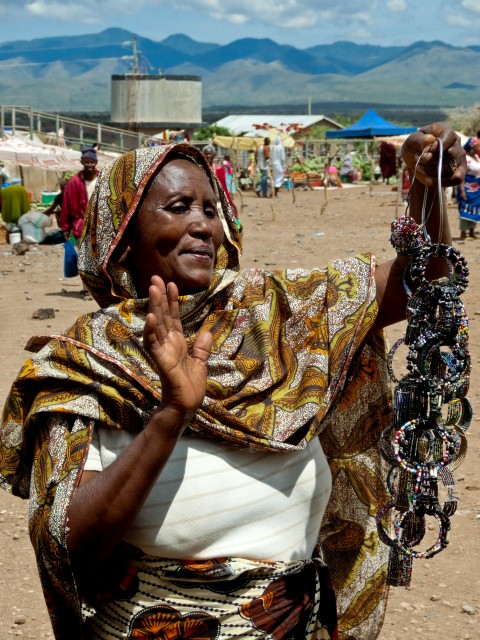 A Tanzanian woman holding some jewelry.