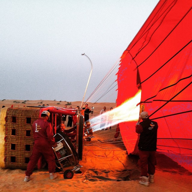 The crew blasts hot air into the envelope to inflate the balloon for take-off.