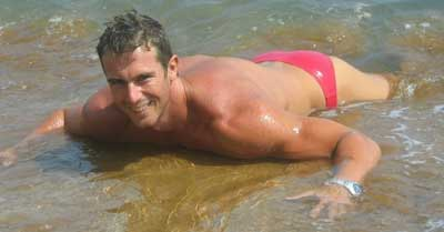 Masculine guy wearing red speedos.
