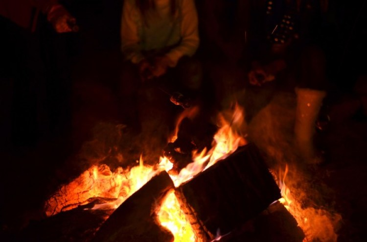 Friends gather around the yule log at the Trail of Lights in Wimberley to make smores. Ready-to-roast smores can be purchased at the event for just a buck. Photo: Shea Carley