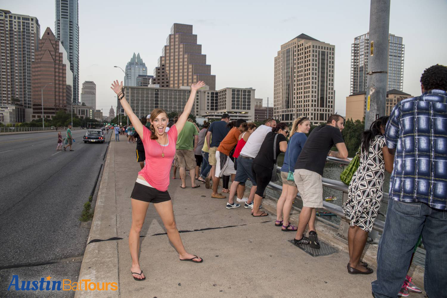 Cheerful attractive Austin tourist waves with excitement and joy while waiting for the bats to take flight on the Congress Avenue Bat Bridge