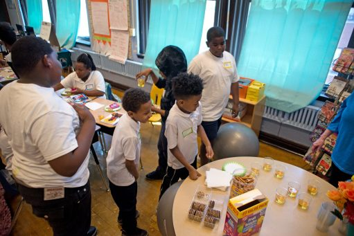 Students go up and grab some snacks to eat while reading the book together last Friday, during a book launch party at Ella Flagg Young Elementary School in Austin. | ALEXA ROGALS/Staff Photographer
