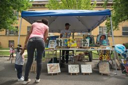 Graphic designer Caleb Harris stands at his booth as attendees look at artwork on Saturday, July 28, 2018, during the Awesome Austin Art Affair on West End and Mayfield Avenues in Austin. | Photos by ALEXA ROGALS/Staff Photographer