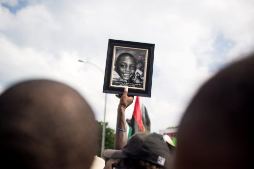A marcher holds up a picture of a child who was killed on Thursday, during an anti-violence protest in Chicago. | ALEXA ROGALS/Staff Photographer