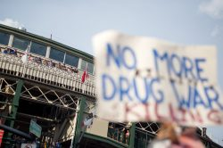 Protesters hold up signs at Wrigley Field attendees watch on Thursday, during an anti-violence protest in Chicago. | ALEXA ROGALS/Staff Photographer