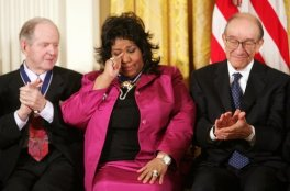 Franklin wipes a tear after being given the Presidential Medal of Freedom on November 9, 2005, at the White House. She is seated between fellow recipients Robert Conquest (left) and Alan Greenspan.