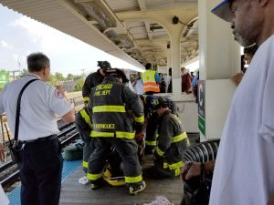 RESCUE: Emergency personnel attend to a woman who jumped onto the tracks at the Central Avenue Green Line stop on Sept. 17. | TIMOTHY INKLEBARGER/Staff