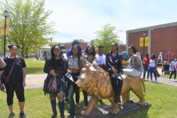 """TAKING IT ALL IN: Students pose on top of the University of Arkansas at Pine Bluff's iconic statue of their mascot the """"Golden Lion."""" 