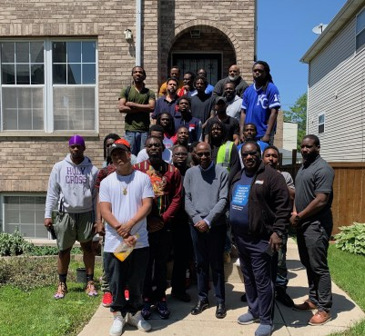 A COMMUNITY TO CALL THEIR OWN: Marshall Hatch Jr. (far right) and Marshall Hatch Sr. (third from left), with the third Maafa cohort outside one of their residential houses on Washington. | BONNI McKeown/Contributor