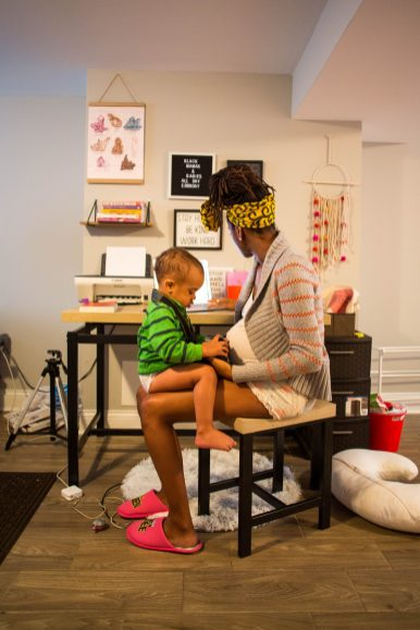 "Tayo Mbande, 25, founder of Chicago Birthworks Collective, a collective of birth workers, healers and wellness practitioners serving Black families across Chicago, working with her son at her home office. ""Being a Black doula working with Black people is very different than being a white doula working with anyone who's not Black,"" she said. ""That person is dealing with generations and generations and generations of women that look like them being told, like you're not in control of your body, and you're not competent enough to be in control of your body."""