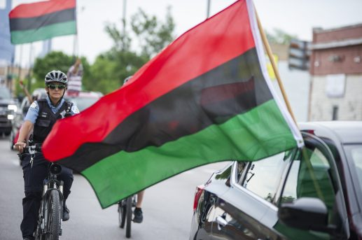 Chicago police officers ride bikes along the parade as African flags are waved from vehicles on Saturday, June 15, during the fifth annual African-American Awareness and Appreciation Parade Juneteenth Celebration on Madison Street on Chicago's Westside. | ALEXA ROGALS/Staff Photographer