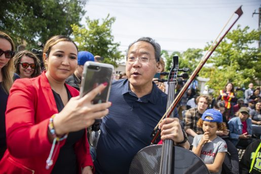 Cellist Yo-Yo Ma, right, takes photos with attendees last Friday, June 21, during the Yo-Yo Ma's Day of Action at Unity Park in Chicago's Homan Square neighborhood. | ALEXA ROGALS/Staff Photographer