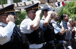 Chicago Police officers salute the flag during the garden's June 14 grand opening ceremony. | MAIA McDONALD/Contributor