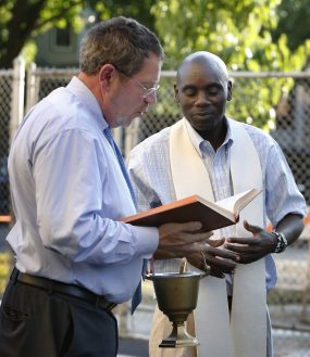 Tom Zbierski, Senior Director, Scholarship Programs and School Relations for Big Shoulders Fund reads scripture as Fr. George Omwando, pastor at the parish prepares to bless the new playground at St. Catherine St. Lucy School, 27 Washington Blvd in Oak Park. The school received a donation from Enchanted Backpack and Big Shoulders to complete the first playground in the school's history. | | Archdiocese of Chicago