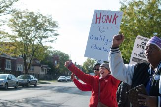 A group of John Hay teachers and support staff engage with drivers traveling on Laramie. | SHANEL ROMAIN/Contributor