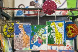 Stained glass artwork from students hang near the entrance on Nov. 15, during an open art theater for the West Side Cultural Arts Council at the Garfield Park Gold Dome in Chicago. | ALEX ROGALS/Staff Photographer