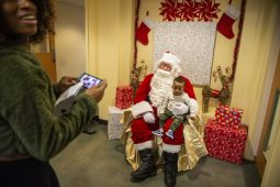 Nasir Brooks takes a photo with Santa Claus on Dec. 16, during a toy drive and holiday party at New Moms in Chicago's Austin neighborhood. | ALEX ROGALS/Staff Photographer