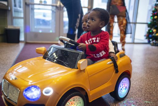 King Lee rides in a children's car on Dec. 16, during a toy drive and holiday party at New Moms in Chicago's Austin neighborhood. | ALEX ROGALS/Staff Photographer