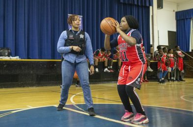 Bonding: Officer Tutwiler, of CPD district 11, guides players with their shots on Dec. 19, during youth basketball training from the Chicago Westside Police at Genevieve Melody Public School in Chicago. | ALEX ROGALS/Staff Photographer