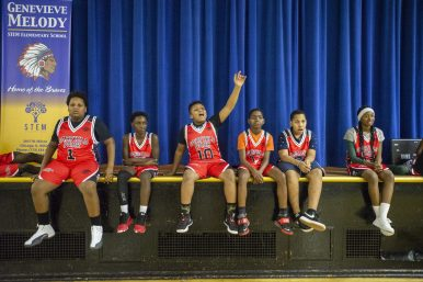 A group of kids from the Garfield Park league watch a scrimmage on Dec. 19, during youth basketball training from the Chicago Westside Police at Genevieve Melody Public School in Chicago. | Photo by ALEX ROGALS/Staff Photographer