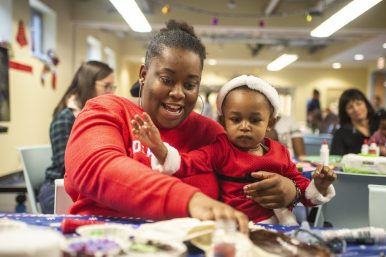 Tierra Collins, left, makes a cookie with Mia Richardson on Dec. 16, during a toy drive and holiday party at New Moms in Chicago's Austin neighborhood. | Photo by ALEX ROGALS/Staff Photographer