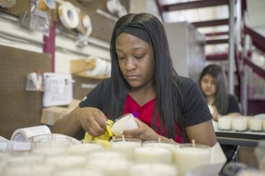 Working mom: Team lead Terrah' Davis, inspects the candles at Bright Endeavors in Chicago's Garfield Park neighborhood. | ALEX ROGALS/Staff Photographer