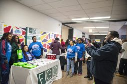 Volunteers and guests from the Family Guidance Centers, Inc. take photos together and hang out grab bags to attendees on Saturday, Feb. 15, during an NBA All-Star viewing party and Census Jumpoff at Collins Academy High School in Chicago. | ALEX ROGALS/Staff Photographer