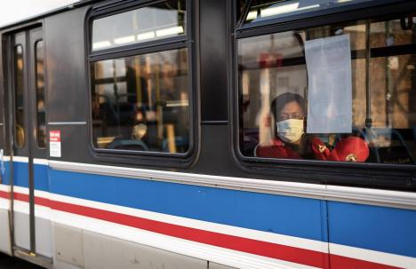 """Karen Williams, 57, rides a CTA bus next to a sign instructing riders to """"Please Practice Social Distancing."""" Williams takes two buses from her home in the Englewood neighborhood each day to care for two elderly clients, work the state has deemed essential during the novel coronavirus pandemic. 