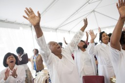 """Mother Lula Robertson raises her hands as the congregation sings """"Pray for Me."""""""