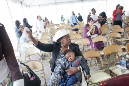 A child sleeps in his grandmother's arms during the tent revival.