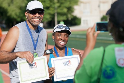ayne and Melissa Johnson pose for a friend after the married couple were first-place finishers. Melissa was the overall female winner while Wayne was first in the 50-59 age bracket.