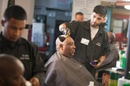 Ernesto Medina brushes loose hairs from the forehead of a customer. (David Pierini/staff photographer)