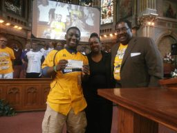 Pastor Hatch greets Darion Radcliff of the Jackie Robinson West team, and his mother with a check
