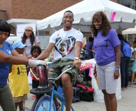Evan Turner and his Aunt Rep. Camille Y. Lillie, and vice president of external affairs at Loretto Hospital, test out a new smoothie maker exercise machine, which was one of the exciting attractions provided by The University of Illinois at Chicago.