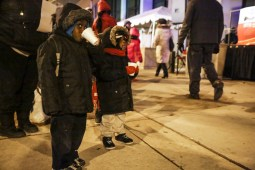 Two kids attempt to stay warm as they watch the Austin Chamber of Commerce's 10th Annual Tree Lighting, outside the 15th District Police Station, 5701 W. Madison, on Thursday, December 4, 2014. | Chandler West/Staff Photographer